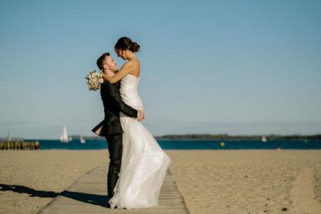 Bräutigam hält Braut auf den Armen am Strand in Travemünde
