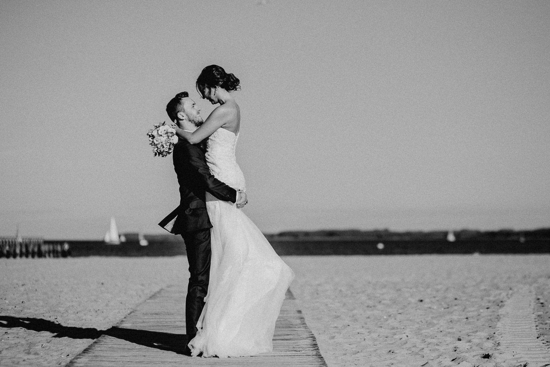 Bräutigam hat die Braut hochgehoben am Strand